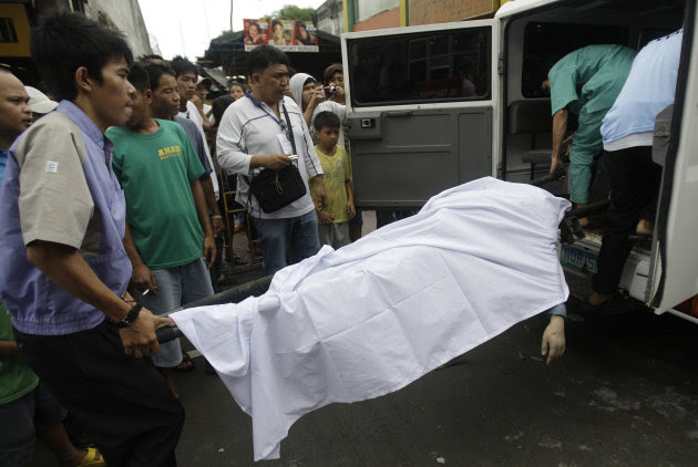 Funeral workers carry the body of a man who was recovered from the rubble of a collapsed wall in suburban Novaliches, Quezon City, Philippines, Sunday Aug. 28, 2011. Slow-moving Typhoon Nanmadol remai