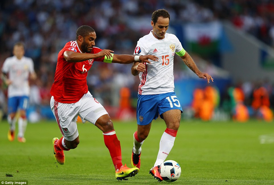 Wales skipper Williams (left) goes toe-to-toe with Russia's captainRoman Shirokov during the first period of the Group B game