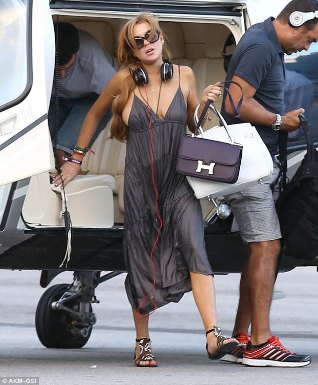 Careful! Lindsay Lohan nearly slipped out of her dress as she stepped off a helicopter in Florianopolis, Brazil on Saturday