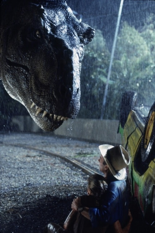 Famous still from Jurassic Park. Grant and Lex huddle by the destroyed tour vehicle while a tyrannosaur eyes them down.