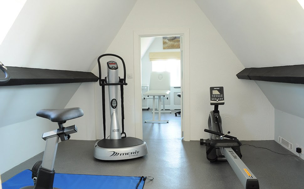 The modern-looking gym at Happisburgh Manor features a rowing machine and a bike. It also has a massage bed in the adjacent room
