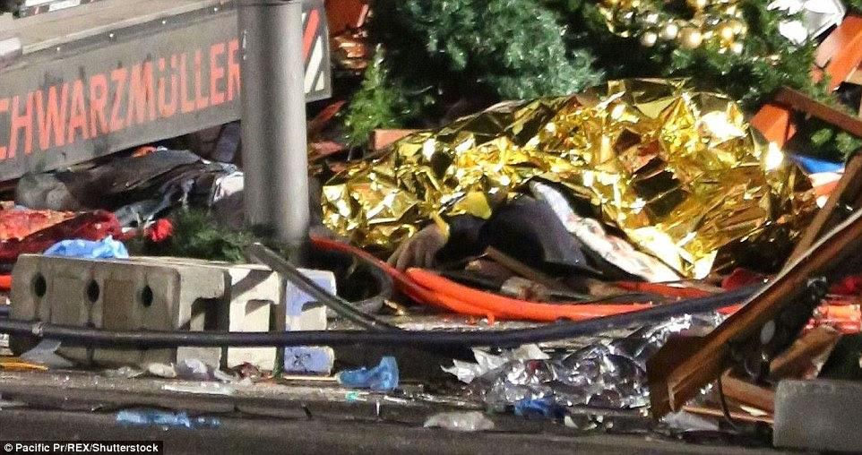 Vítima: Um corpo arrastado sob as rodas do camião encontra-se coberto com um cobertor de ouro esta manhã na parte traseira do camião roubado