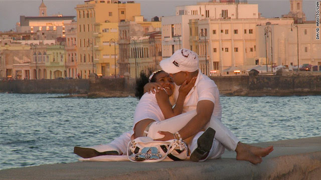 A young couple embraces at sunset along the Malecon in Havana, Cuba.