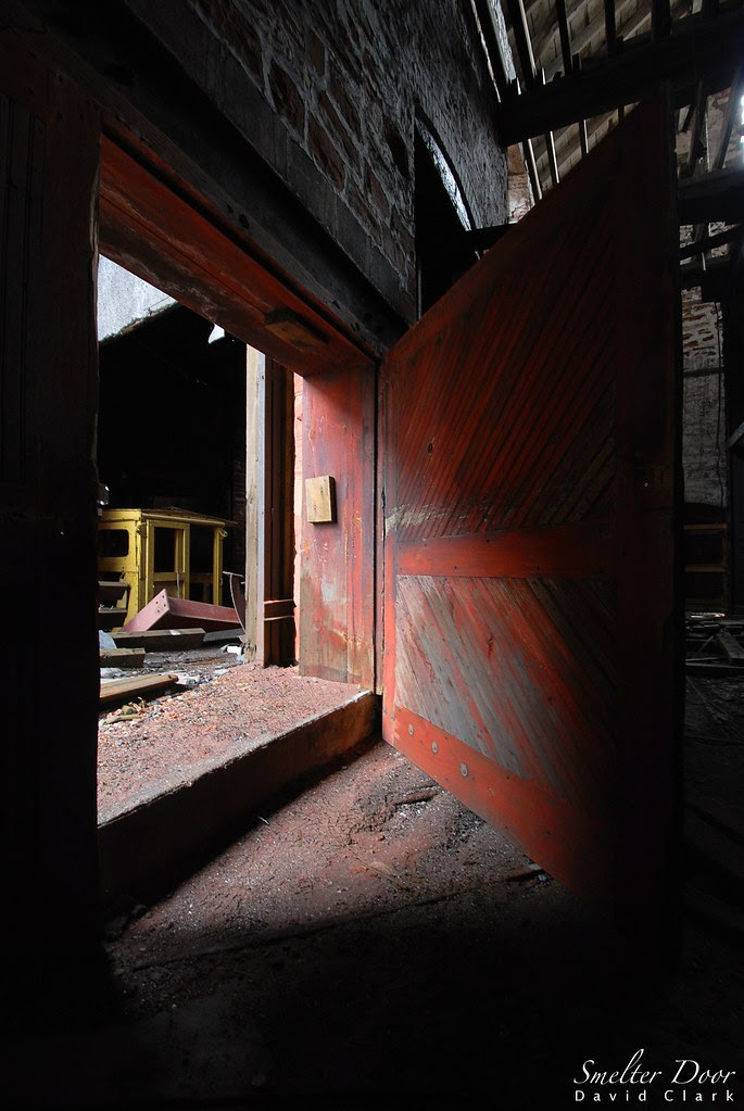 A red wooden door leading from a dark room into a lit courtyard.