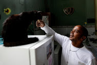 Former prisoner Jose Menendez gives a piece of cheese to his cat Nelly after an interview at his home in Havana, Cuba, Wednesday Dec. 28, 2011. Menendez, 46, is among the prisoners being released after Cuba's President Raul Castro announced on Dec. 23 the pardoning of 2,900 prisoners. Menendez, who served 26 years of a 44-year sentence, was originally sentenced to two years for illegally discharging a firearm when he was 19-years-old. Subsequent charges were filed against him for crimes he is said to have committed while incarcerated, adding the additional 42 years to his two-year sentence. (AP Photo/Franklin Reyes)