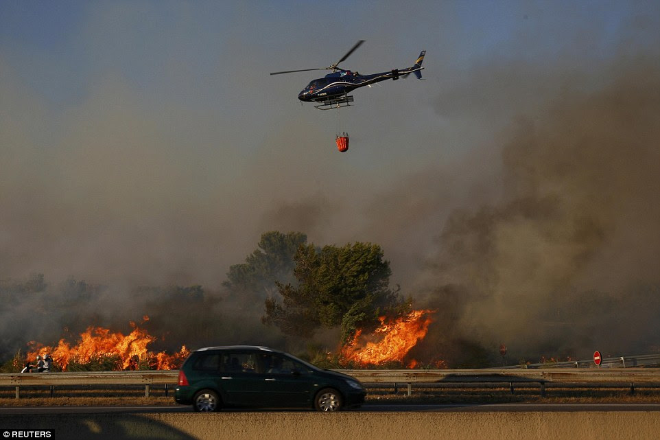 Um helicóptero prepara para apagar incêndios que queimam ao lado de uma auto-estrada com produtos químicos especiais