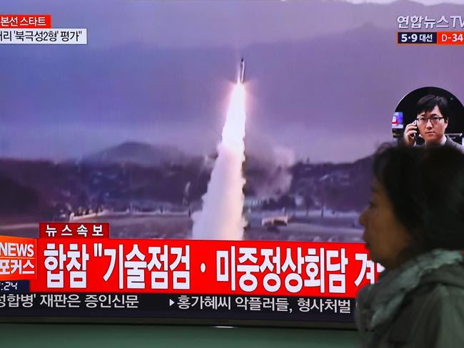 A woman walks past a television screen showing file footage of a North Korean missile launch, at a railway station in Seoul on April 5. Picture: AFP