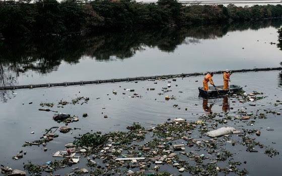 """Trabalhadores retiram o lixo retido na """"eco-barreira"""" na entrada da Baía de Guanabara, em Duque de Caxias, no Rio (Foto: YASUYOSHI CHIBA / AFP)"""