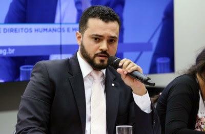 Foto mostra debatedores na mesa de abertura da audiência pública