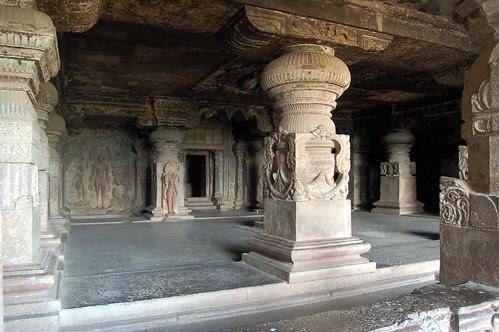 Reich verzierte Säulen tragen die Halle, im Hintergrund der Eingang zum Schrein, links neben den Schrein die Darstellung des Mahavirs, wie er von Pflanzen umschlungen wird.