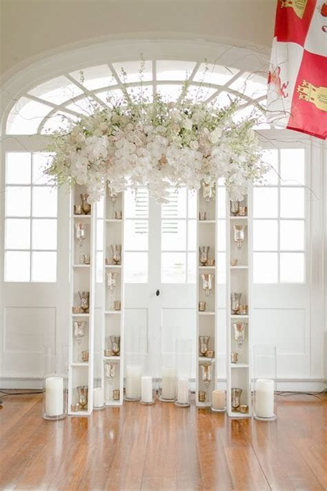 Unique modern altar of bookcases and a floral arch ~ https