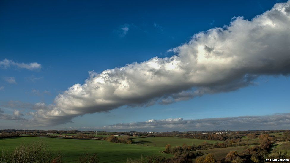 A line of white fluffy cloud in countryside on a bright day