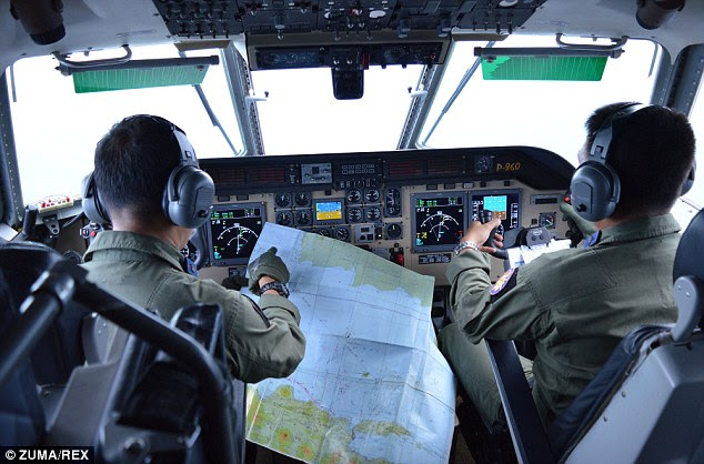 An Indonesia Navy search and rescue crew looks for AirAsia QZ 8501 on a Maritime Patrol Navy Aircraft above Bangka-Belitung Islands in the Java Sea