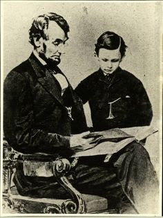 """An 1864 Mathew Brady photo depicts President Lincoln reading a book with his youngest son, Tad"""