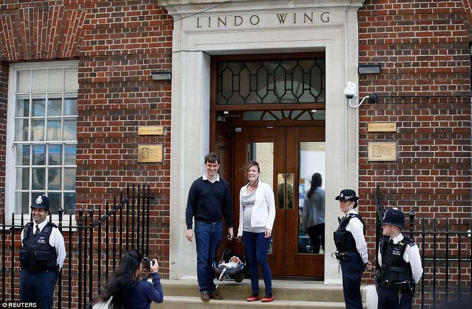 Una pareja desprevenida salió del Lindo Wing con su bebé recién nacido para ser recibida por los medios de comunicación del mundo.  Posaron para fotografías afuera de la famosa puerta frente a docenas de periodistas y fotógrafos antes de partir en un taxi.