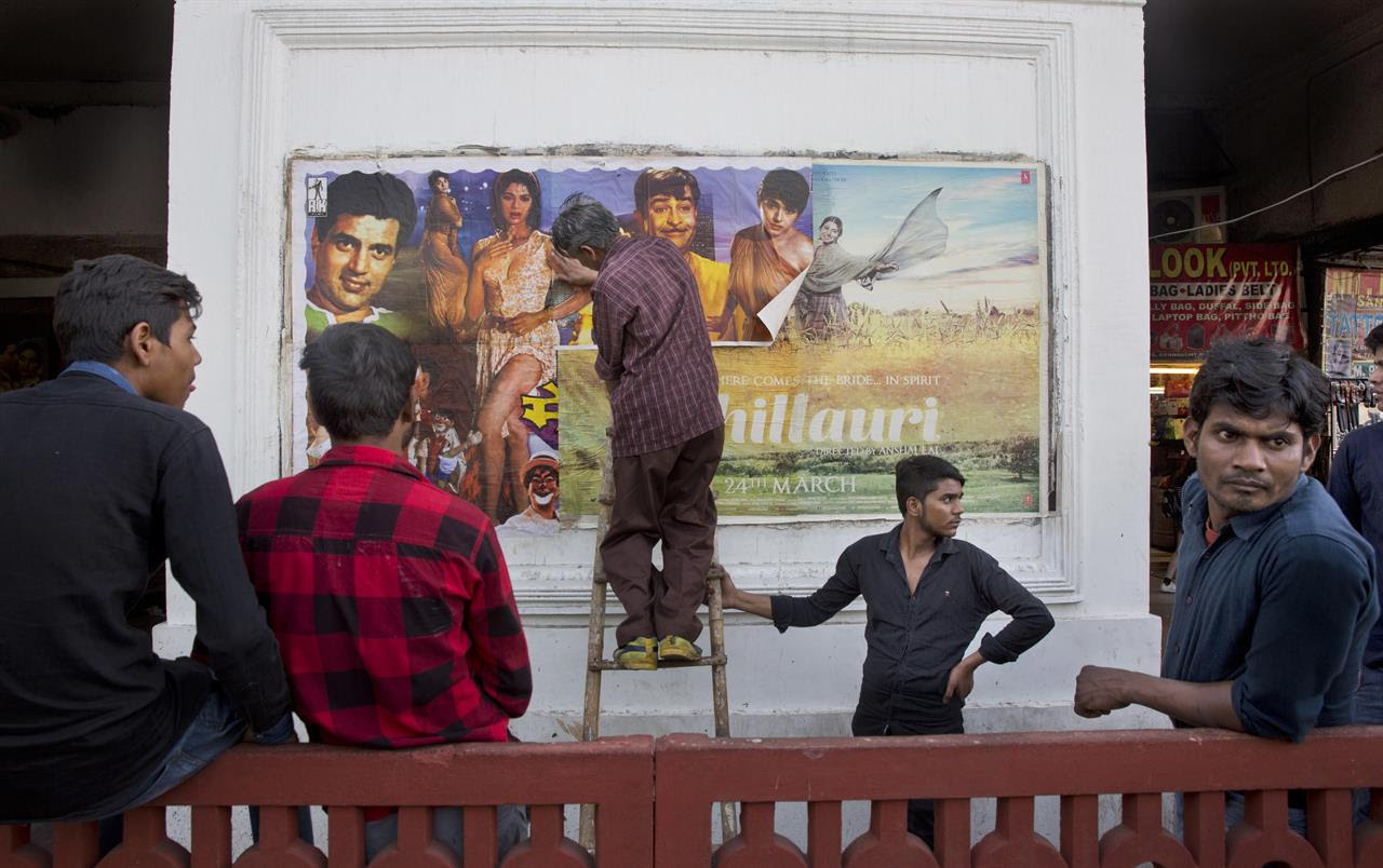 In this Wednesday, March 29, 2017 photo, employees paste for the final time a poster of an old Bollywood classic film on the top of a new released film outside Regal Theater in New Delhi, India. The Indian capital's iconic theater signed off on Thursday night after more than eight decades with nearly 600 movie buffs cheering a 1964 Bollywood classic at a final screening. It's expected to make way for a multiplex from a single screen.
