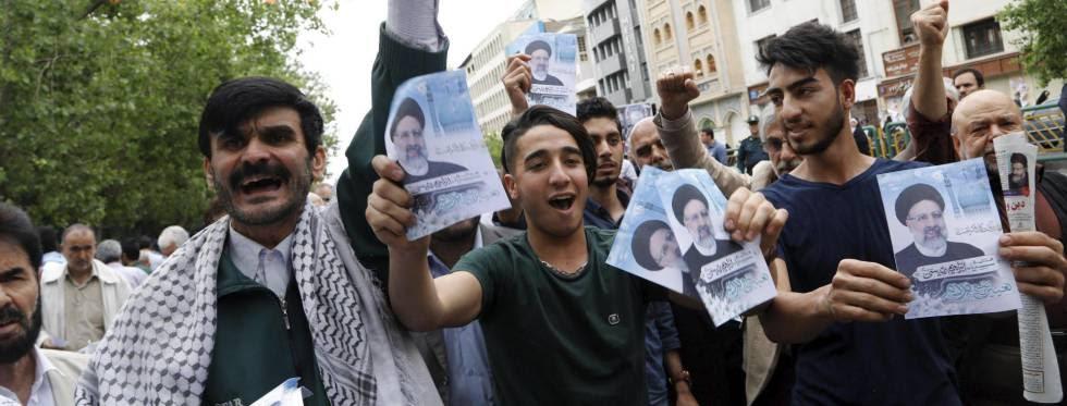 Ciudadanos muestran carteles del candidato Ebrahim Raisí.