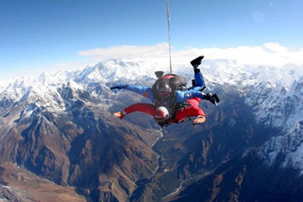Tandem skydivers soar high above the Himalaya Mountains.