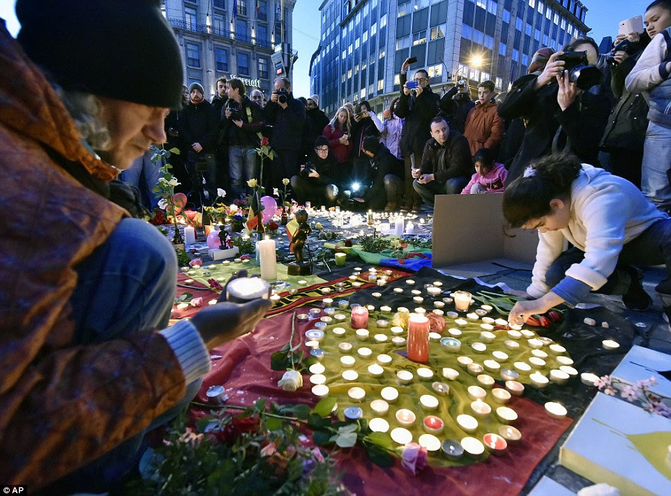 In honour and memory: Scores of people bring flowers and candles to mourn for the victims at Place de la Bourse in the centre of Brussels