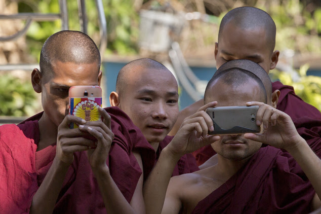 Monks in Myanmar taking photos of Richard Blackwood. Perceived insults to religion are taken seriously in the mostly Buddist country