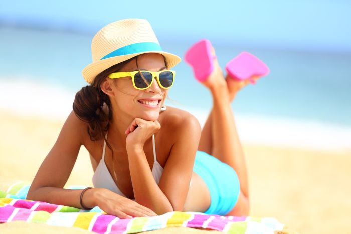 Beach woman funky happy and colorful wearing sunglasses and beach hat having summer fun during travel holidays vacation. Young multiracial trendy cool hipster woman in bikini lying in the sand.
