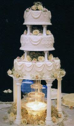 Monogrammed wedding cake with glass pillars filled with