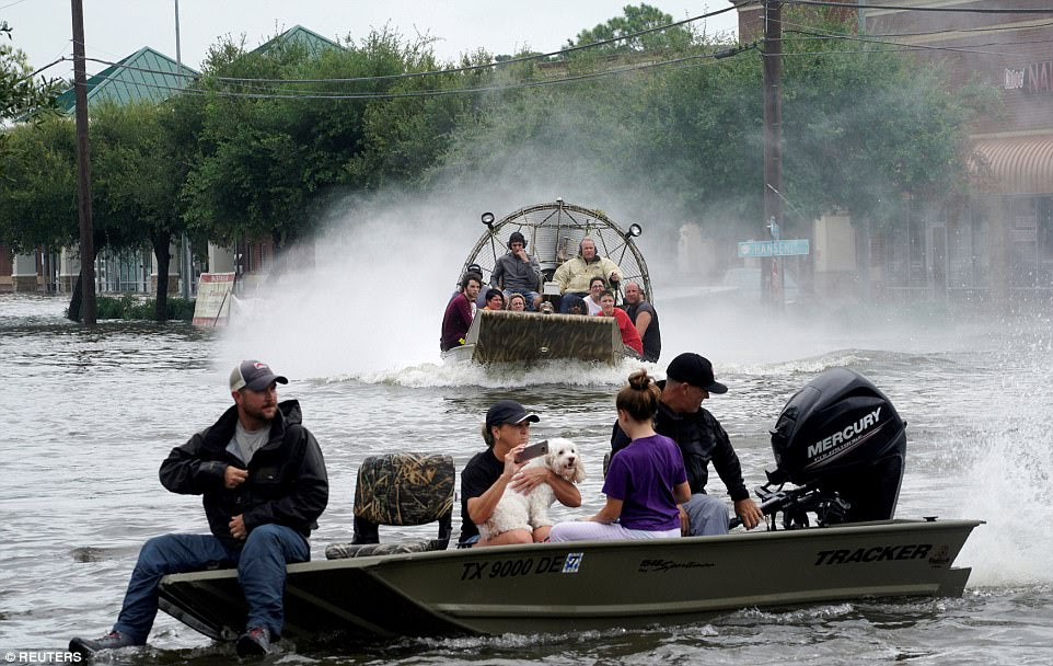 Residents have turned to social media with pleas for help as the Houston police department asked any civilians with boats to join them and assist with the more than 2,000 calls for rescues. Pictured: People in Dickinson, outside of Houston, on Sunday