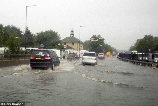 Driving rain: Roads in and around London were also flooded, with motorists on the A41 near Hendon struggling to get through the downpour