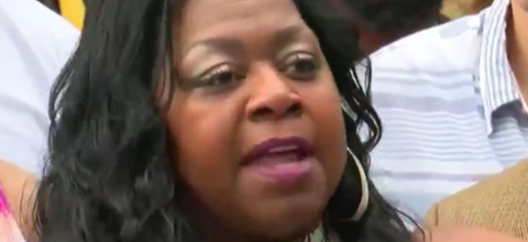 A Black woman with long hair speaks angrily