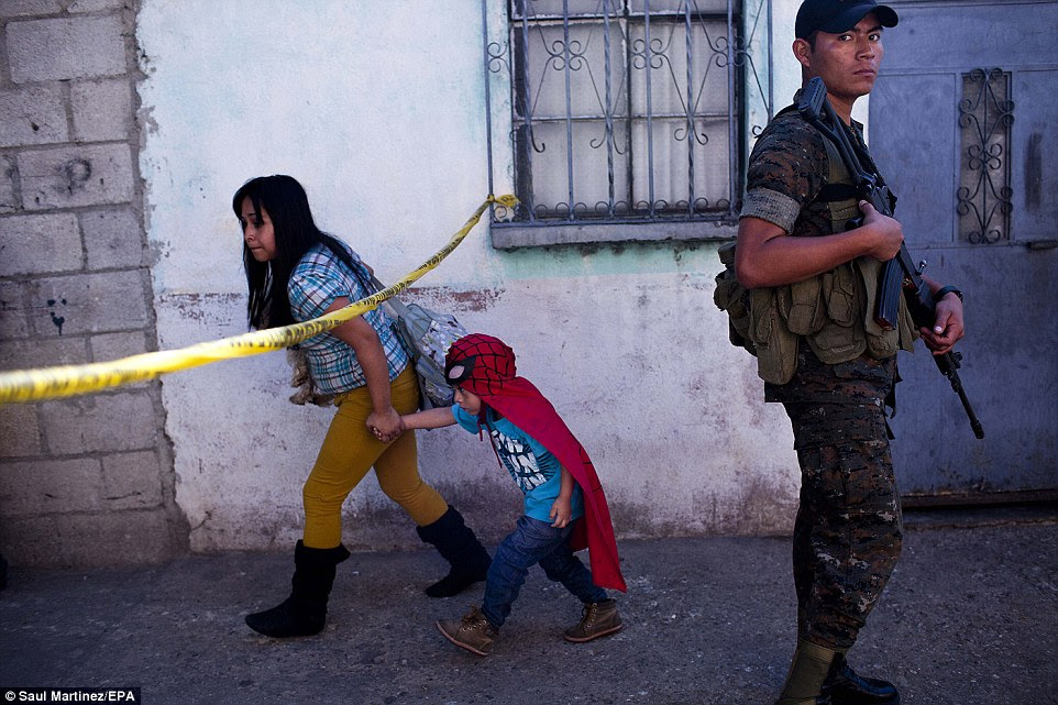 Crime-fighting: A boy dressed as Spider-Man walks under police tape near his home while an armed soldier stands guard at the scene