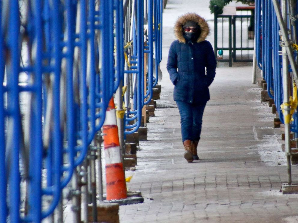 PHOTO: A woman is bundled with a scarf and hood as she walks through a construction area in downtown Pittsburgh with temperatures in the single digits, Jan. 5, 2018.