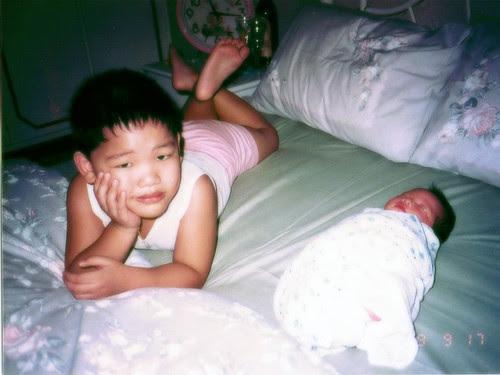 Posing whilst newborn sister is sleeping.