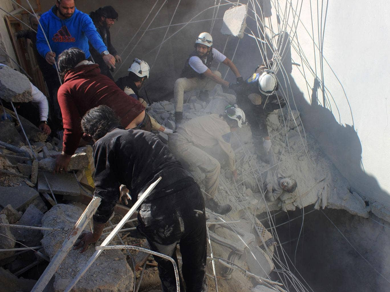 Members of the civil defence pull a boy out from under the rubble of a building following air strikes by suspected Russian warplanes backing the Syrian government on the Sahour neighbourhood of the northern Syrian city of Aleppo on February 16, 2016.