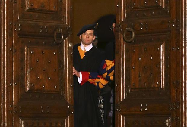 Membro da Guarda Suíça fecha as portas da residência papal de verão, em Castel Gandolfo, para marcar o fim do pontificado de Bento XVI, nesta quinta-feira (28) (Foto: AP)