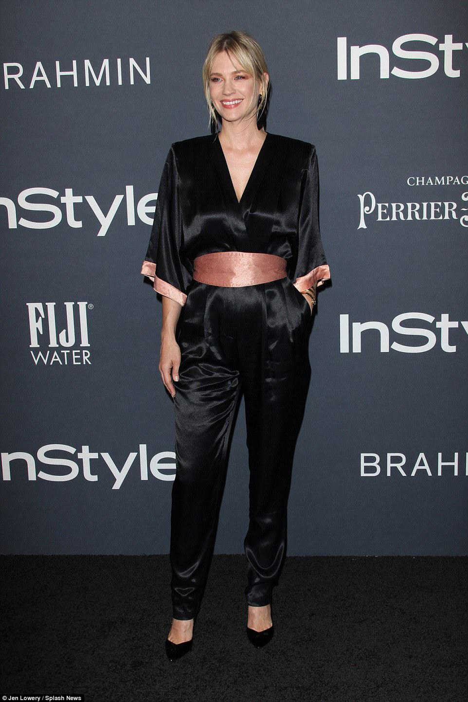 Blonde beauty: January Jones, 39, was sleekly styled in a black satin jumpsuit with a pink band at the waist and pink cuffs on the half sleeves. She added a pair of black pointed toe heels