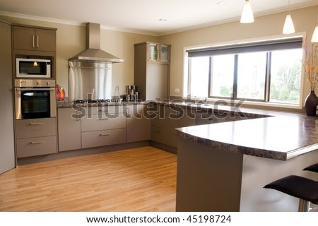 A Large Modern Kitchen With Stainless Steel Accessories And Wooden