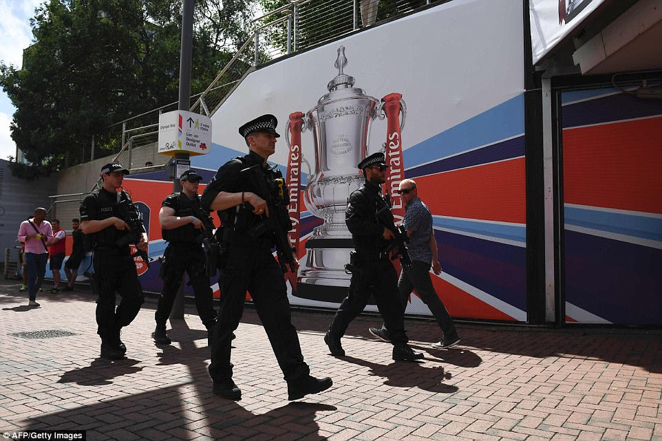 Armed police patrol their way down Wembley Way towards the stadium on a sunny day in north west London