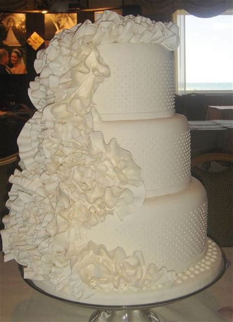 Three tier round white wedding cake with ruffles (1