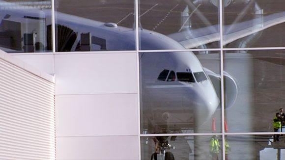 Lentokoneen puolittaisprofiili heijastuu Helsinki-Vantaan lentoaseman isoihin ikkunoihin.