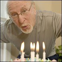 Photo: A man blowing out candles on a birthday cake.