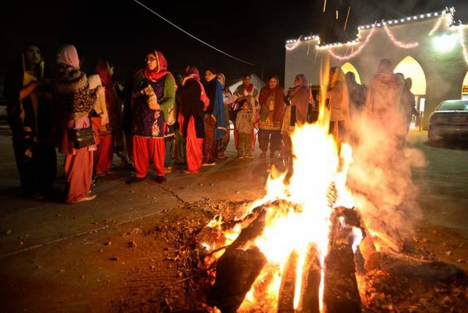 People gather around the fire during Lohri, a Punjabi festival, in Livingston on Tuesday.