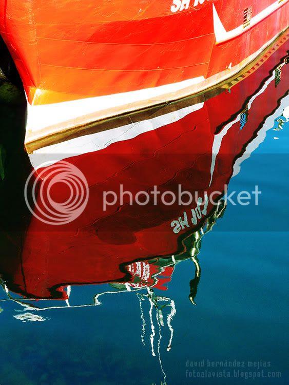Reflejos en el agua de un barco amarrado en un puerto del mar de Islandia
