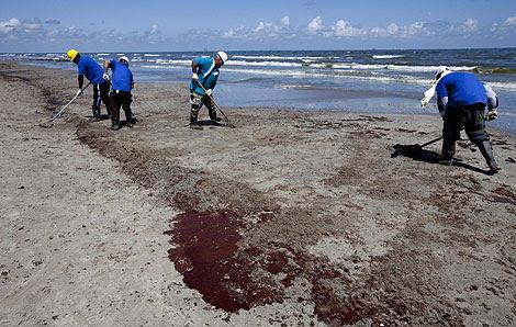 Operarios limpian los restos de crudo en la costa. | Efe