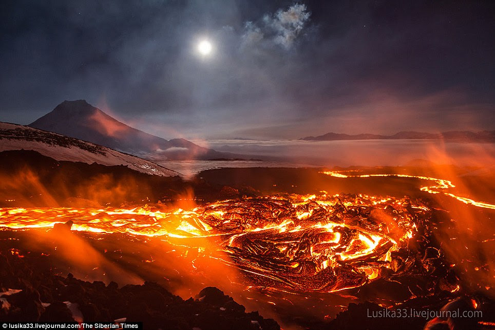 Kingdom of lava: The volcano spills over in a river of molten rock underneath a bright full moon