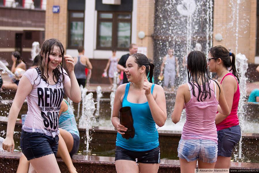 Девушки в насквозь промокшей одежде у фонтана