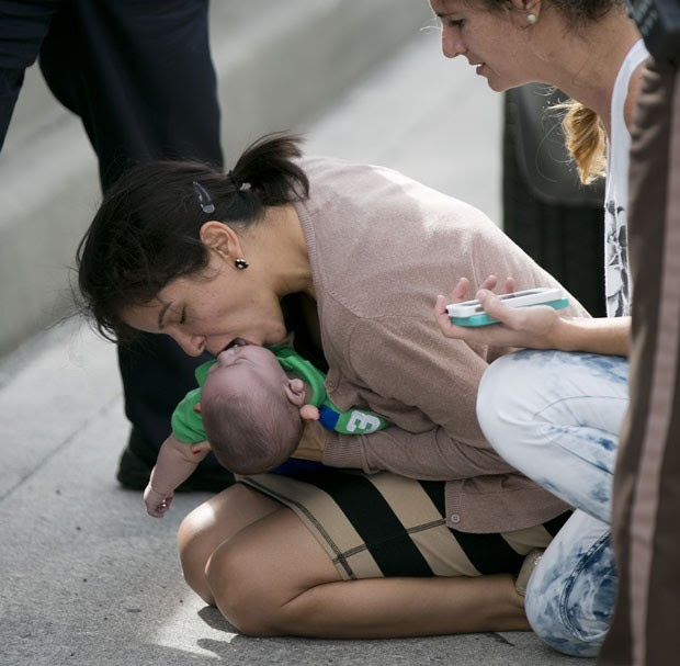 Pamela Rauseo tenta fazer seu sobrinho de 5 meses voltar a respirar no meio de rodovia nos EUA (Foto: The Miami Herald, Al Diaz/AP)