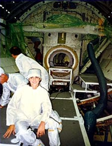 Nicole Stott working inside shuttle payload bay.