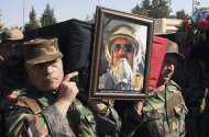 "In this photo taken during a government-organized tour for the media, Syrian army officers carry the coffin of one of the 17 army members, including six elite pilots and four technical officers who the military said were killed in an ambush on Thursday during their funeral procession, in Homs province, Syria, on Saturday Nov. 26, 2011. The military blamed terrorists for the ambush and has vowed to ""cut every evil hand"" that targets the country's security. Syria is facing mounting international pressure to end a bloody crackdown on an uprising against the rule of President Bashar Assad that the U.N. says has killed more than 3,500 people. The Arab League was meeting Saturday to consider the possibility of sweeping economic sanctions. (AP Photo/Bassem Tellawi)"