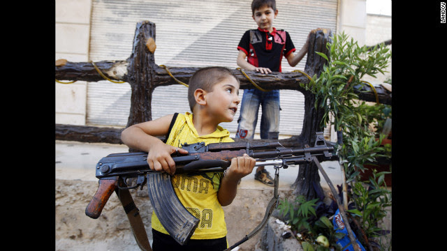 A boy plays with an AK-47 rifle owned by his father in Azaz, some 29 miles north of Aleppo on Friday, August 3.