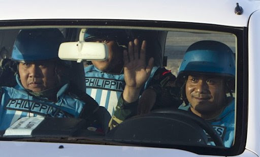 Filipino UN peacekeepers cross the Quneitra checkpoint in the Israeli-occupied Golan Heights on March 9, 2013